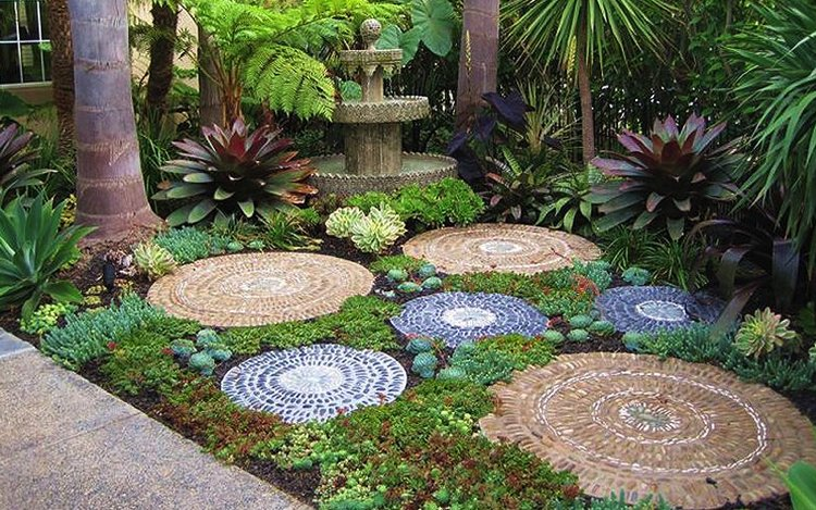 Gorgeous Pebbled mosaic medallion stepping stones merge perfectly with their tropical background.