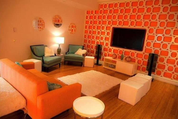 Classic furnishings and an elegant suite are made alive with brave orange wall accents, a truly lively living room.