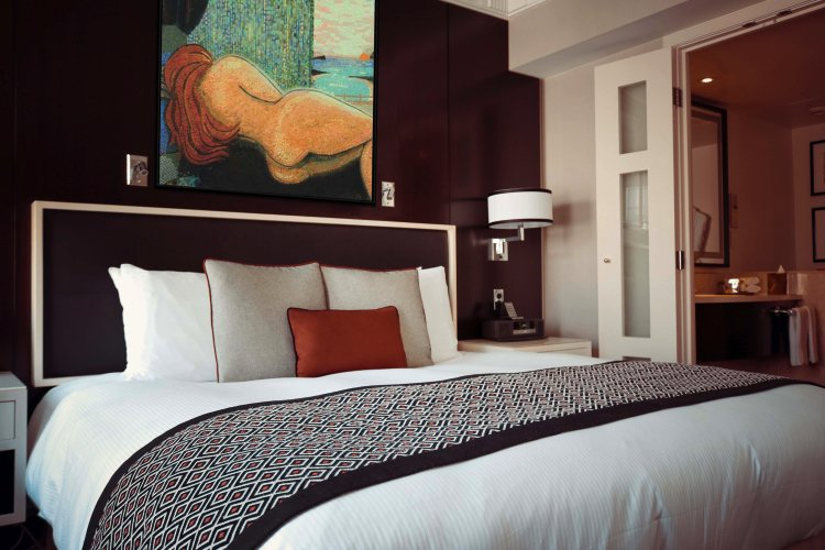 Figurative nude mosaic art above the bed.