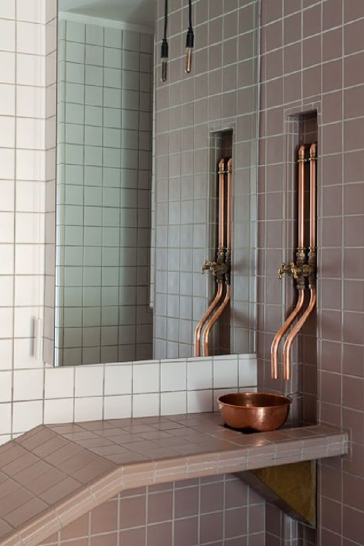 Earthy tiles with exposed copper pipes as a home accent