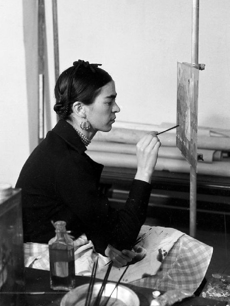 Frida painting in her studio